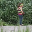 Stock Video: Little girl running from left to right and backward several times