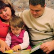 Father and mother with little daughter read book - Stock Photo