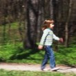 Stock Video: Girl goes towards boy on bicycle on forest road in spring