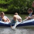Stock Video: Family with 4 kids in rubber boat, rowing