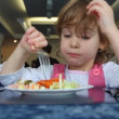 Stock Video: Small girl eats salad in café