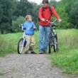 Mwith boy talking, then riding on bicycles in park — Stock Video #13787606