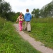 Boy and girl join hands walking in park, from camera - Stockfoto
