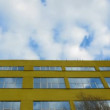 Stock Video: Over the yellow house clouds float and are reflected in house windows