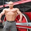 Shirtless bodybuilder stands on railroad against locomotive — Stockvideo
