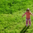 Little girl waving hands and jumping on green grass — Stock Video
