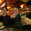 Stock Video: Three men clink glasses goblet with beer