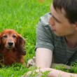 Man lying on green grass talking with dog - Stockfoto