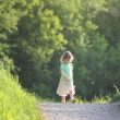 Girl walking on road with toy - Foto de Stock
