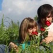 Young man and girl smelling flowers and kissing each other - Stockfoto