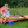 Boy puts on a life jacket sitting on an inflatable rubber dinghy - Stock Photo