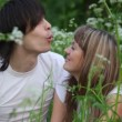Young man and girl blowing dandelions on each other and laughing - Stockfoto