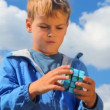 Stock Video: Portrait of boy solves earth cube in park