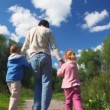 Father rotating with daughter and son outdoor — Stock Video