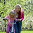Ma teaches girl to roll on bicycle - Stock Photo