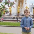 Stock Video: Boy and girl playing and throwing flower petals in front of soviet fountain