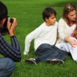 Stock Video: Father photographs mother and daughter with the son sits on field in park