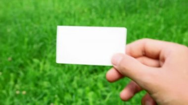 Male hand holding business card on grass — Stock Video #13786458