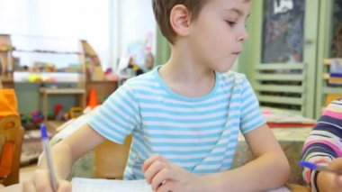 Boy sitting in the classroom and watching to the left — Vídeo stock