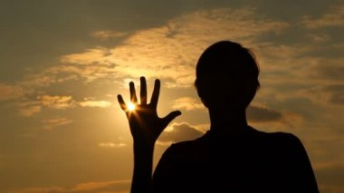 Silhouette of man which palm closes sun — Stock Video