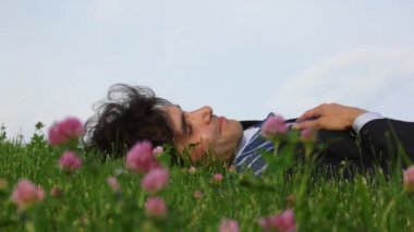 Happy handsome man lying on green grass and field flowers — Stock Video