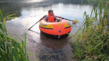 Garoto remando um barco inflável da costa — Vídeo Stock