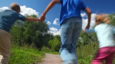 Father with son and daughter running in park, join hands, from camera — Stock Video