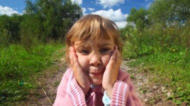 Portrait of little feeling girl in park — Stock Video