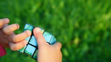 Little girl solves rubik's cube on green grass background — Stock Video