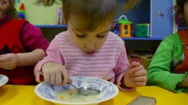 Niña comiendo gachas de avena en el jardín de la infancia — Vídeo de stock