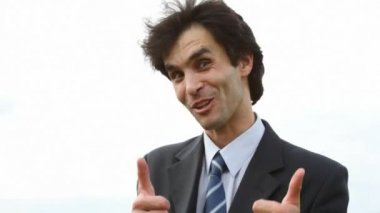 Happy handsome man in suit speaking to camera — Stock Video