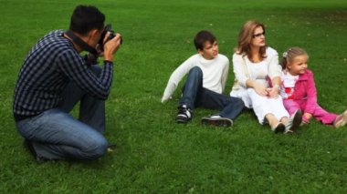 Father photographs family from mother and daughter with the son sits on field in park — Stock Video
