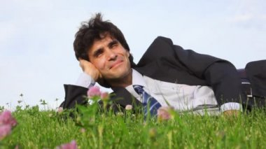 Happy handsome man lying on green grass — Stock Video