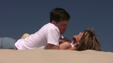 Couple laying on the sand, she caress his face — 图库视频影像