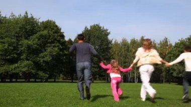 少年と少女の手を維持する家族公園の前方を走る — ストックビデオ