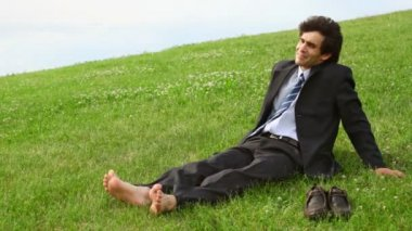 Handsome man without shoes sitting on green grass — Stock Video