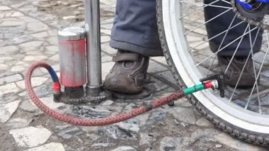 Boy's foot on air-pump, pumping bicycle wheel — Wideo stockowe