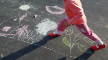 Little girl walking on drawing on asphalt — Stock Video