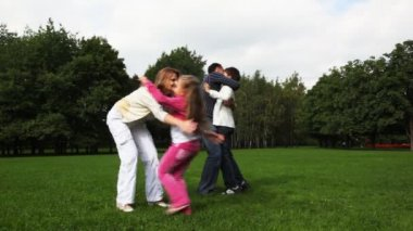 Family with boy and girl embraces, kisses, turnes on field in park — Stock Video