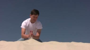 Young man making the sandhill — Stock Video #13787462