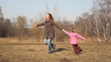 Mother and girl merrily play on glade — Stock Video