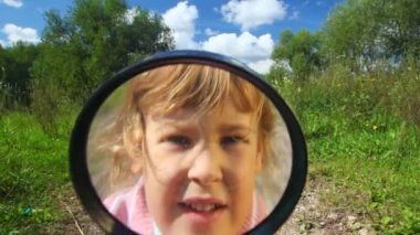 Little girl looks in camera through a magnifier — Stock Video