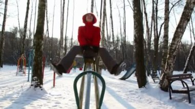 Woman in red coat rocks on winter seesaw — Stockvideo