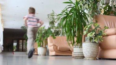 Boy runs away through hall — Stock Video