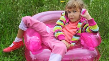 Little girl with telephone sitting on inflatable armchair — Stock Video