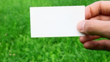 Male hand holding business card on grass — Vidéo