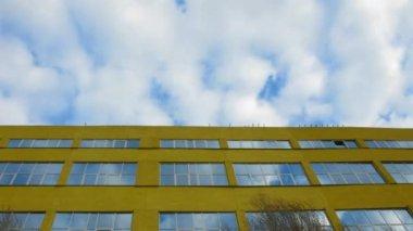 A casa amarela são e flutuar nuvens refletidas windows em casa — Vídeo stock