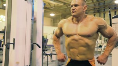 Bodybuilder straining muscles in gym — Stock Video