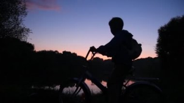 Boy with rucksack on bicycle looks at sunset lake — Stock Video