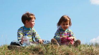 Chlapec a dívka sedí na poli a diskuse — Stock video